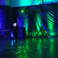 The DJ's at a formal eighth grade dance with green uplighting