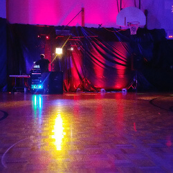 The DJ's at a formal eighth grade dance with red uplighting